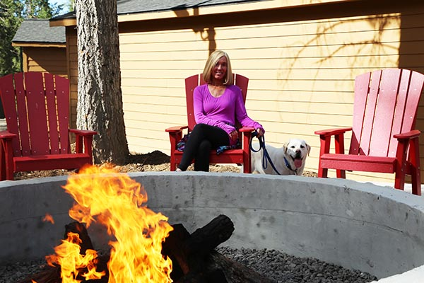 woman and dog by firepit